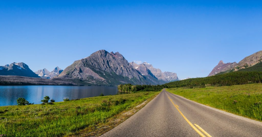 Scenic road next to a lake with a mountain in the background representing MT 200